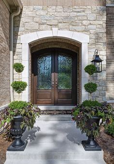 DH Custom Homes, custom Pendleton in Chesterfield, MO. As you enter the home, you are welcomed by a beautiful pair of arched, stained mahogany doors with iron glass inserts. That's what we call a warm, and beautiful, welcome! #entry #frontdoor #door
