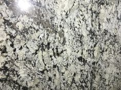 Delicatus granite slap, the Jackson Pollock of stones. White base with veins of variant greys, bits of black and specs of vibrant quartzite. Lots of movement, but when paired with simple cabinets this stone can shine as a natural art form and focal point.
