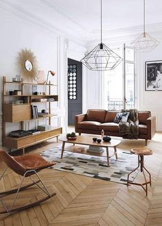 The mixing of shapes (hexagonal lamp, angled wood floor, striped carpet) adds visual interest to this living room