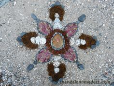 Mandala Art Medium: ~~peach stone, golden rock, grey stone, olive rock moss, pink stem leaf, pink/green seed pods and speckled granite on river sand canvas~~