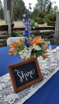 Blue Delphinium, peach and white alstromeria, wax flower, seeded eucalyptus,  mason jar painted gold with burlap wired ribbon bow centerpiece.