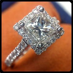 Diamonds set around this Princess cut diamond create a stunning halo effect