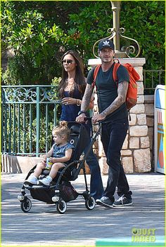 david victoria beckham disneyland family trip 01 David Beckham pushes his two-year-old daughter Harper in a stroller while spending the day at Disneyland with his wife Victoria Beckham and their kids on Thursday…