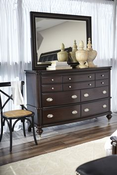 Spirited curves contrast with sleek lines to create the Esquire Merlot dresser and mirror's gorgeous style. Though based on traditional designs, there's still plenty of room for contemporary expression. Brushed nickel carries through the set, from nailhead trim to the chic hardware.