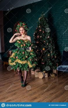 Photo about Beautiful young girl in a Christmas tree costume, standing in the Studio next to an artificial Christmas tree. Image of year, standing, costume - 133512365 Christmas Tree Costume, Studio, Image, Beautiful, Dresses, Fashion, Vestidos, Moda, Fashion Styles