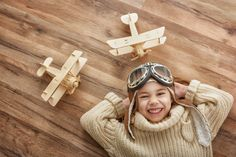 girl playing with toy airplane by choreograph. happy child girl playing with toy airplane. the dream of becoming a pilot