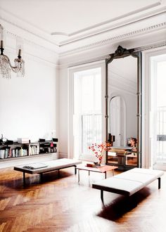 Floor to ceiling mirror in sleek, minimalist living room with bench seating.