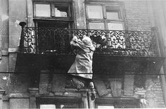 A woman hangs from a balcony, preparing to drop to the street and the waiting SS.