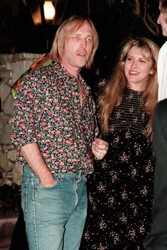 Tom Petty holding hands with Stevie  ~ ☆♥❤♥☆   who's wearing a casual long-sleeved floral dress