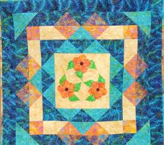 """Hawaiian Quilt Pattern """"Hibiscus"""".  The Hibiscus are appliqued on by machine.  Gorgeous Batiks make up this quilt."""