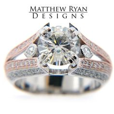 Matthew Ryan Design Engagement Ring MRD001 - Matthew Ryan Design Engagement Ring  General Information:  Metal: 14KT White & Rose Gold  Side Stone Information:  Diamonds Shape: Round and Marquise Side Diamond Total Weight: 0.75 carat  Center Stone Information:  Holds an 8.00 mm Charles and Colvard Moissanite Center     Other Information:  Also available in 18KT White or Yellow Gold and in Platinum. Please call us for pricing 1 (888) 774-4367