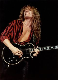 "John Sykes on stage with Whitesnake in 1984, shortly after joining the band.    John Sykes was the epitome of the 80s journeyman guitarist, playing with Tygers of Pan Tang, Thin Lizzy and Whitesnake.     Having been hired by David Coverdale in 1983 for Whitesnake's ""Slide it in"" tour, he re-recorded a few guitar tracks for the US version of the album and went on to co-write much of Whitesnake's 1987 eponymous album.    However before touring it, David Coverdale fired the entire"