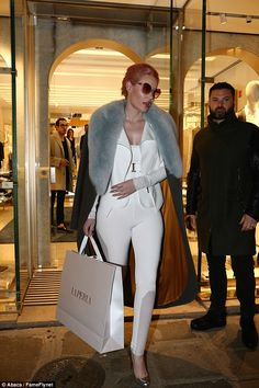 One shopping trip, two outfits: Iggy left the boutique dressed in an all-white ensemble wi...