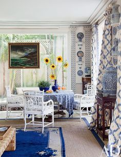 Boldly patterned curtains join painted bamboo chairs and a Maurice de Vlaminck seascape.