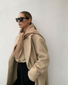 Minimalist Look Idea: Mathilde Jensen in square cat-eye sunglasses, a beige coat, camel sweater tied over the shoulders, and black pants Source by lefashion Coats Beige Outfit, Neutral Outfit, Look Zara, Mantel Beige, Stylish Winter Outfits, Outfit Winter, Office Outfits Women, Beige Coat, Beige Sweater