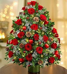 Holiday Flower Tree®️️ Luxury - three dozen fresh red or multicolored roses, baby's breath, boxwood and assorted Christmas greens is in a glass vase, decorated with ornaments and lights. Full-size arrangement measures approximately x Christmas Flower Arrangements, Christmas Flowers, Beautiful Flower Arrangements, Love Flowers, Floral Arrangements, Christmas Decorations, Holiday Decor, Flowers Nature, Cemetery Flowers
