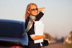 Fashion business woman with financial papers next to her car stock photo