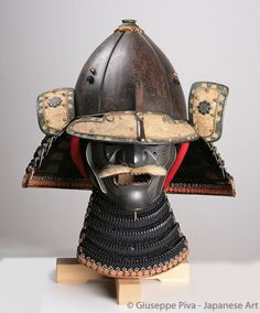 """Kabuto and menpo from an Okegawa-do tosei gusoku, 17th century (early Edo period)  """"Kabuto signed Joshu no ju Saotome Iesada.  The heavy five-plates kabuto is in fact of a rare elongated shape (shiinari, """"acorn-shaped"""") and is signed by Iesada, one of the three important smiths of the Saotome family, active during the first part of the Edo Period."""" - giuseppepiva.com"""