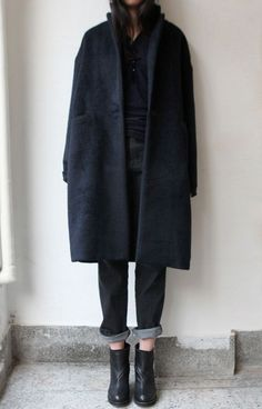black overcoat, cuffed denim, ankle boots.