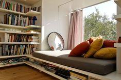 coin de lecture en face de la fenêtre avec étagères du sol au plafond faites sur mesure et miroir rond