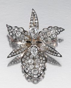DIAMOND BROOCH, CIRCA 1880.  Designed as an orchid flower head close-set with cushion-shaped and rose-cut diamonds, highlighted by two principal pear-shaped stones, French assay marks, maker's marks, original fitted case from Grognier-Arnaud, Lyon, original stem deficient, flower head adapted.