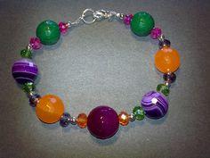 Bracciale composto da agata striata viola, giada arancione, radice di smeraldo, agata fucsia e cristalli, montato con componenti in metallo color argento. Realizzazione artigianale.
