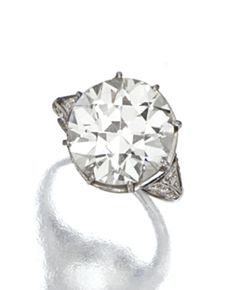 DIAMOND RING, CIRCA 1930 The old European-cut diamond weighing 8.80 carats, the tapering shoulders enhanced with small single-cut diamonds, mounted in platinum
