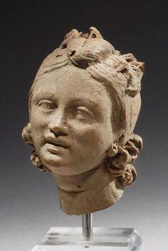 HELENÍSTICO CABEZA_datado en la segunda mitad del siglo II a.C., presenta una cabeza rodeada de una guirnalda; debió formar parte del borde decorativo de un emblema central.