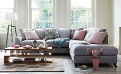 mixed pastel trend in living room with slouchy corner sofa and pink cushions