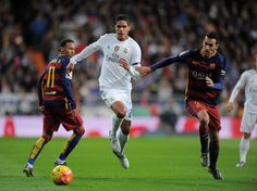 Rafael Varane of Real Madrid is tackled by Sergio Busquets of FC Barcelona during the La Liga match between Real Madrid and Barcelona at Estadio Santiago Bernabeu on November 21, 2015 in Madrid, Spain.