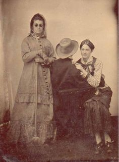 three people -interesting photo - one lady holding a broom and one a flower. Dark glasses, the man's back. I can think up all kinds of stories to go with this photo. Very interesting. You really must click on the link and see the other unexplained photos. Oh my!