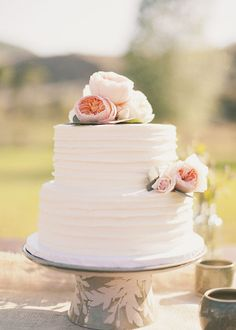 White two tier wedding cake with textured frosting and flowers