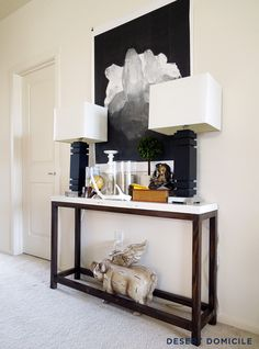 Build a custom console table to fit behind the sectional for a fraction of the price.  The one pictured here cost $18.