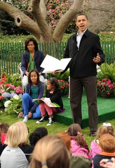 U.S. President Barack Obama (R) reads a book to a group of children, as first lady Michelle Obama (L) and their daughters Sasha Obama (2R) and Malia Obama sit with him, during the annual White House Easter Egg Roll