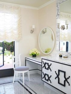 Hollywood regency bathroom features a steel framed window dressed in a ruched ivory shade over ivory walls and gray marble tiled floors boasting a geometric white and gray tiled rug framed by a black marble border.