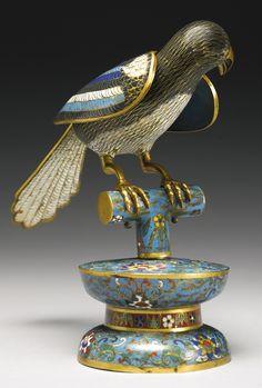A CLOISONNE-ENAMEL FIGURE OF A MAGPIE ON A STAND QING DYNASTY, 18TH CENTURY cast with head lowered and turned to the side, the black body and white breast with gilt cloisons defining the plumage, the wings brightly enameled,  the bird standing on a cylindrical perch atop and waisted pedestal enameled with stylized lotus scrolls on a turquoise ground