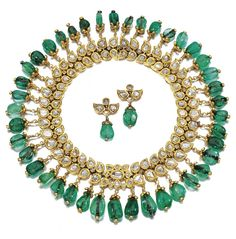 Indian emerald and diamond necklace, circa 1900. Photo courtesy of Sotheby's. Designed as a fringed collar of foliate design, decorated with rose cut diamonds in a kundun setting, supporting a graduated fringe of emerald cabochon drops, together with a pair of matching earrings. Signed J. Chaumet.