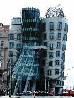 """La """"Casa Danzante"""" en Praga, es un ejemplo de arquitectura deconstructivista construido en 1993. Resalta por sus dos cuerpos centrales. El primero es una torre de cristal que se estrecha hacia la mitad y que está sujeta por pilares curvados. El segundo, paralelo al río, es caracterizado por su forma ondeada y sus ventanas no alineadas. No pasa desapercibido."""