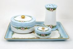 This pretty hand painted dresser set features pretty pink and blue flowers on a white background with light blue trim. The assembled set includes a monogrammed vanity tray by B&C Limoges dated 1912 (1900-1929), a Hutschenreuther Favorite Bavaria covered powder jar and small pin or ring box, circa 1915 and an RS Prussia hatpin holder which dates between 1917 and 1945. The rectangular tray has a gold monogram and is trimmed in gold.  There is wear on the trays gold trim and monogram as well...