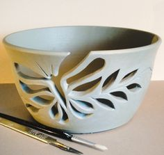 Unfired yarn bowl with a Butterfly and leaves cutout yarn feed. earthwoolfire@gmail.com