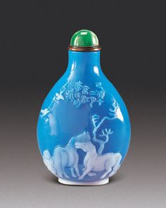 International snuff bottle society. Glass snuff bottle with white overlay on a turquoise ground carved to illustate a boy tending two horses with two swallows above and an inscription, seal Junting, dated 1819. Bloch Collection.