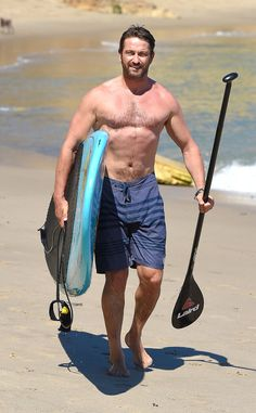 Gerard Butler carrying his paddleboard along the beach in Malibu, CA - Thursday September 25, 2014