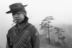 Photographer: Dean Chapman Burma, Tanna Kwei Point, Karenni State (Myanmar) A Karenni soldier awaiting the impending Burma Army offensive. Scattered around the position are the decomposing corpses of scores of dead Burma Army soldiers who failed to capture the position three weeks previously. The wind reeks with the gagging stench of death. This soldier was shot in the shoulder during the offensive that followed. The Burma Army eventually overran the fortification, but not before sustaining…