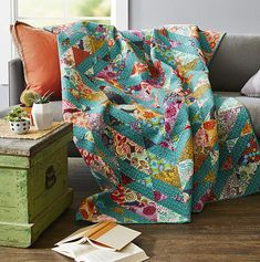 "Bohemian Rhapsody. Pair rich prints with a deep turquoise fabric in one easy block repeated over and over for a dramatic throw. Designers: Jo Kramer and Kelli Hanken of Jo's Country Junction. Finished quilt: 72-1⁄2x84-1⁄2"". Finished block: 6"" square."