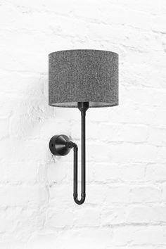 Loft design sconce lamp in black patina metal finish with herringbone tweed custom shade. Here on white brick wall in industrial style coffee bar.