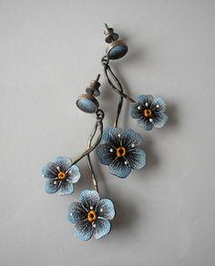 Delikatne kolczyki na sztyft wykonane ze srebra 925 i skóry naturalnej. Kwiaty niezapominajek namalowane ręcznie wodoodporną i odporną na ścieranie farbą w odcieniach błękitu wykończone dekoracyjnymi żyłkami. Srebro matowione, oksydowane na kolory brązu i złota. Całkowita długość kolczyka łącznie z zawieszką wynosi 5 cm