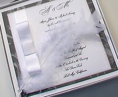 A 4.5x4.5 white line card with a silver border displays your wedding invitation wording and is layered onto a 5x5 graphite metallic cardstock. This renaissance Victorian wedding invitation is embellished with a white grosgrain ribbon tied into a classic bow and a feather with a swarowski crystal accessory.