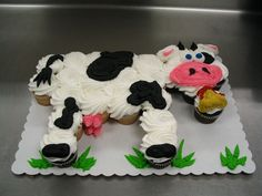 24 cupcakes arranged and iced to form a cow.