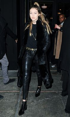 Gigi Hadid wears a black t-shirt, choker, leather pants, a long coat, and ankle boots