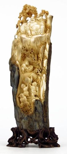 """ANTIQUE CHINESE IVORY VILLAGE TUSK CARVING Monumental, the Best Carving we have Ever Witnessed. Possibly 19th Century. Depicting a Buddha Sitting in a Tree with His Little Children Servants. Tusk Measures Approximately 11"""" Long. Comes in a Fitted Wooden Base."""